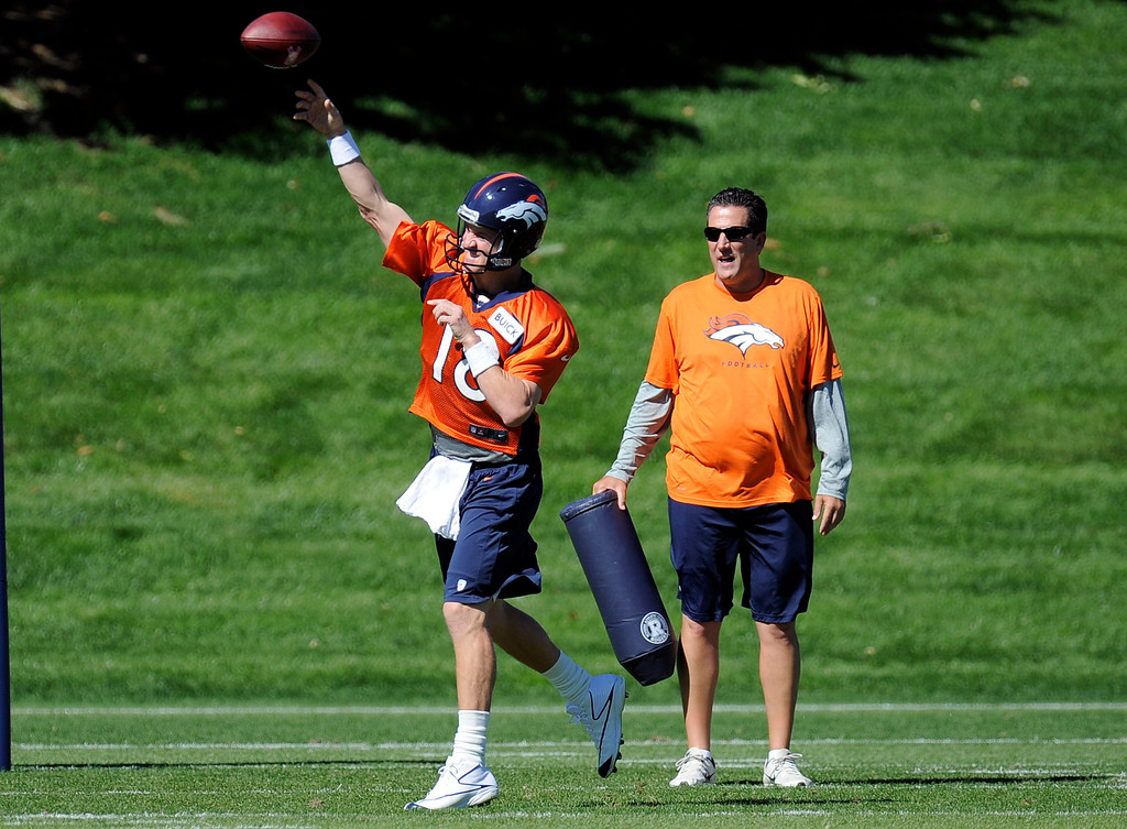 . Quarterback Peyton Manning (18) of the Denver Broncos drops back to pass as Greg Knapp looks on during practice September 25, 2013 at Dove Valley. (Photo by John Leyba/The Denver Post)