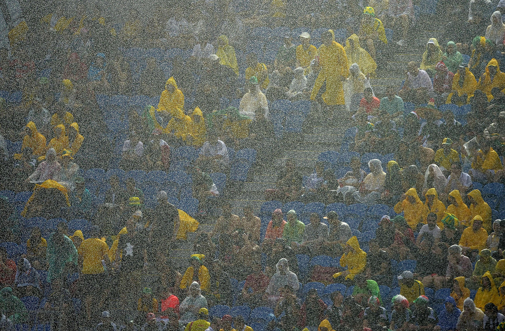 . Football fans sit under pouring rain during the Group A football match between Mexico and Cameroon at the Dunas Arena in Natal during the 2014 FIFA World Cup on June 13, 2014. GABRIEL BOUYS/AFP/Getty Images