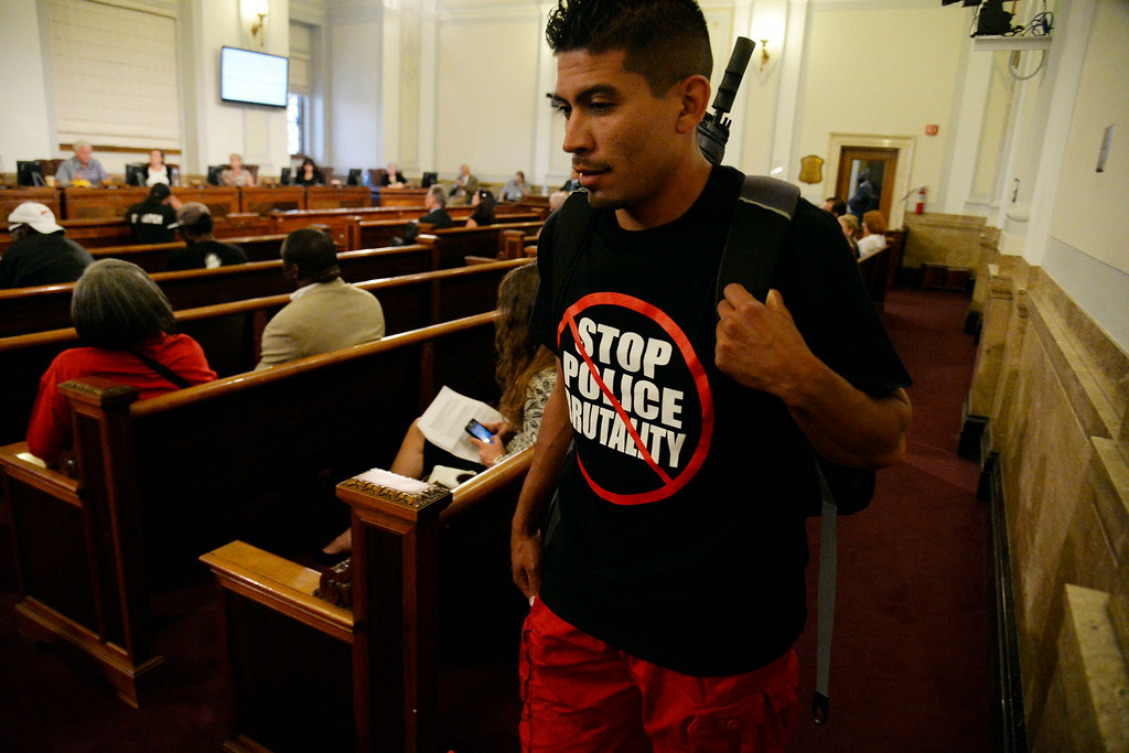 . DENVER, CO - AUGUST 04: Robert Lopez wears a Stop Police Brutality as the city council votes in the settlement with Jamal Hunter. The Denver city council voted 10 to 1 in favor of a $3.25 million settlement in the Jamal Hunter jail abuse case on Monday, August 4, 2014. (Photo by AAron Ontiveroz/The Denver Post)
