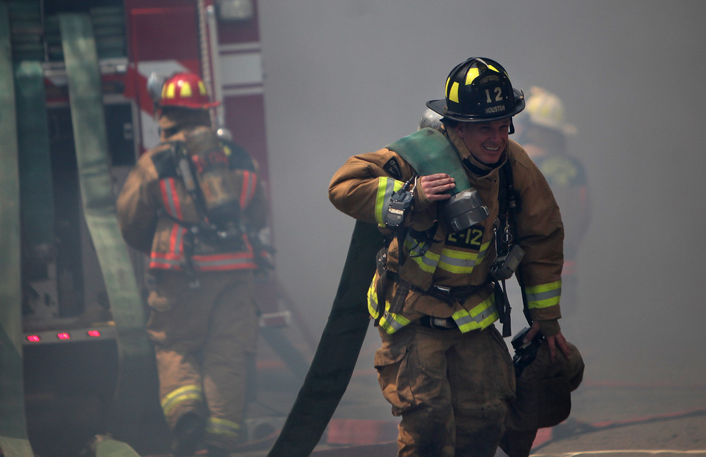 . A firefighters carries an additional water hose to as firefighters work to contain and extinguish a five-alarm fire at a construction site Tuesday, March 25, 2014, in Houston. (AP Photo/Houston Chronicle, Mayra Beltran)