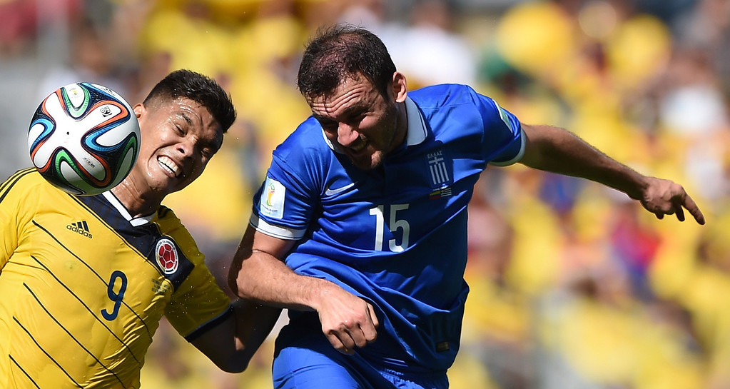 . Greece\'s defender Vasilis Torosidis (R) vies with Colombia\'s forward Teofilo Gutierrez (L) during a Group C football match between Colombia and Greece at the Mineirao Arena in Belo Horizonte during the 2014 FIFA World Cup on June 14, 2014.   AFP PHOTO / EITAN ABRAMOVICH