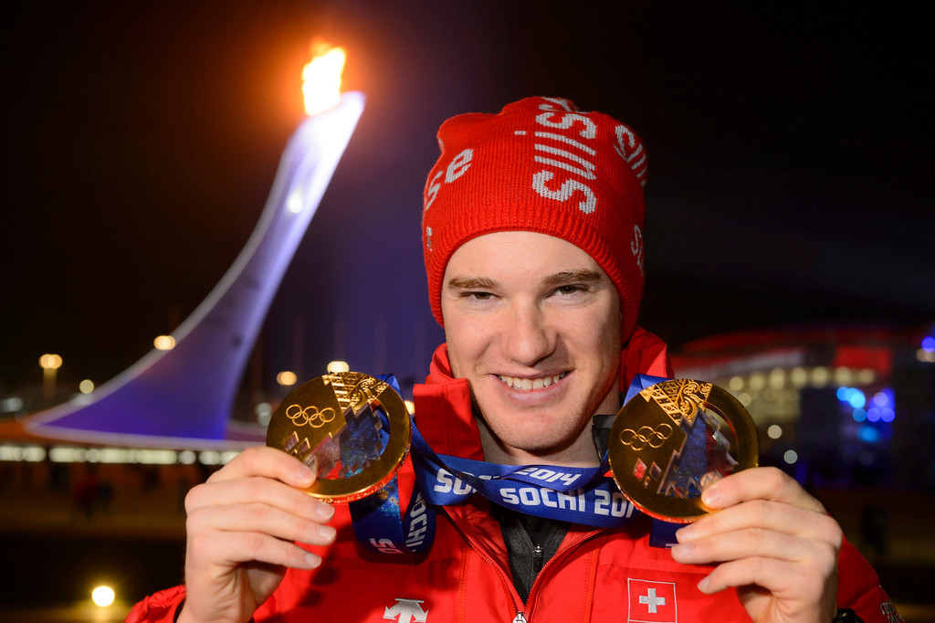 . Cross country skiing 15km classic and skiathlon gold medalist Switzerland\'s Dario Cologna poses with his two gold medals in front of the Olympic Flame after the victory ceremony of the men\'s cross country skiing 15km classic at the Sochi 2014 Olympic Games, Sochi, Russia, 14 February 2014.  EPA/LAURENT GILLIERON