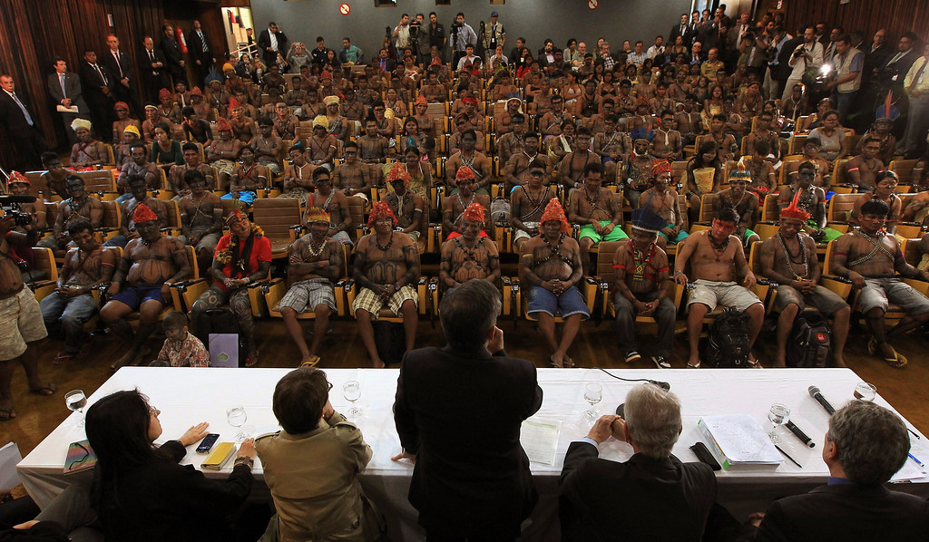 . Minister of the General Secretariat of the Presidency of Brazil, Gilberto Carvalho (C), speaks to Munduruku Indians during a meeting at the Planalto Palace in Brasilia, June 4, 2013. President Dilma Rousseff\'s government sought on Tuesday to defuse mounting conflicts with indigenous groups over its decision to stop setting aside farm land for Indians and plans to build more hydroelectric dams in the Amazon. The government flew 144 Munduruku Indians to Brasilia for talks to end a week-long occupation of the controversial Belo Monte dam on the Xingu river, a huge project aimed at feeding Brazil\'s fast-growing demand for electricity. REUTERS/Ueslei Marcelino