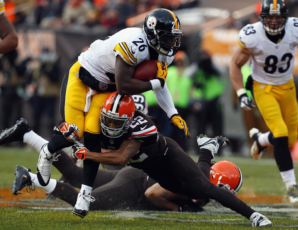 . Running back Le\'Veon Bell #26 of the Pittsburgh Steelers runs the ball as he is hit by defensive back Buster Skrine #22 of the Cleveland Browns at FirstEnergy Stadium on November 24, 2013 in Cleveland, Ohio.  (Photo by Matt Sullivan/Getty Images)