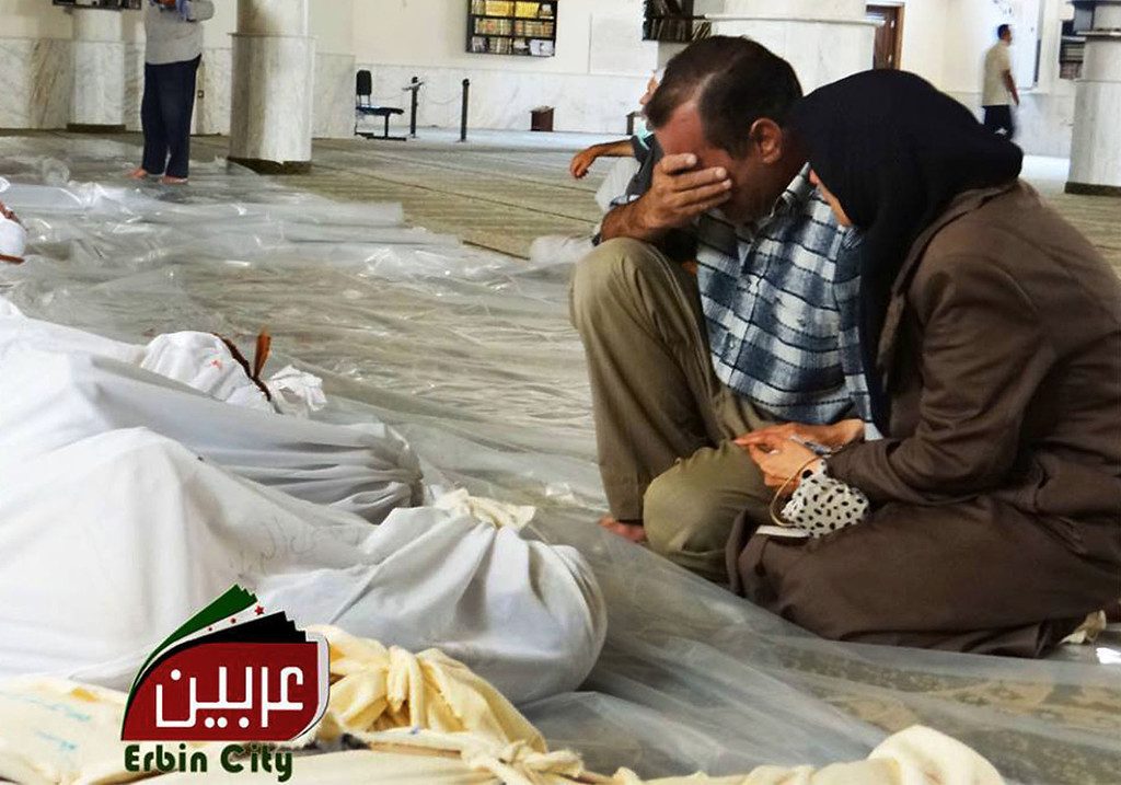 """. In this citizen journalism photo provided by the Local Committee of Arbeen, which has been authenticated based on its contents and other AP reporting, a man and woman mourn over the dead bodies of Syrian men after an alleged poisonous gas attack fired by regime forces, according to activists in Arbeen town, Damascus, Syria, Wednesday, Aug. 21, 2013. Syrian regime forces fired intense artillery and rocket barrages Wednesday on the eastern suburbs of the capital Damascus, in what two pro-opposition groups claimed was a \""""poisonous gas\"""" attack that killed dozens of people. (AP Photo/Local Committee of Arbeen)"""