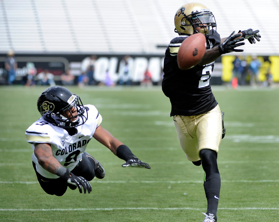 . BOULDER, CO.- APRIL13: Kenneth Crawley, right, tries for the pass intended for receiver Jeff Thomas. The University of Colorado football team hosts its spring football game at Folsom Field under the direction of new head coach Mike MacIntyre. (Photo By Kathryn Scott Osler/The Denver Post)