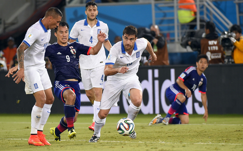 . Japan\'s forward Shinji Okazaki (C) vies with Greece\'s defender Sokratis Papastathopoulos (R) during a Group C football match between Japan and Greece at the Dunas Arena in Natal during the 2014 FIFA World Cup on June 19, 2014. FABRICE COFFRINI/AFP/Getty Images