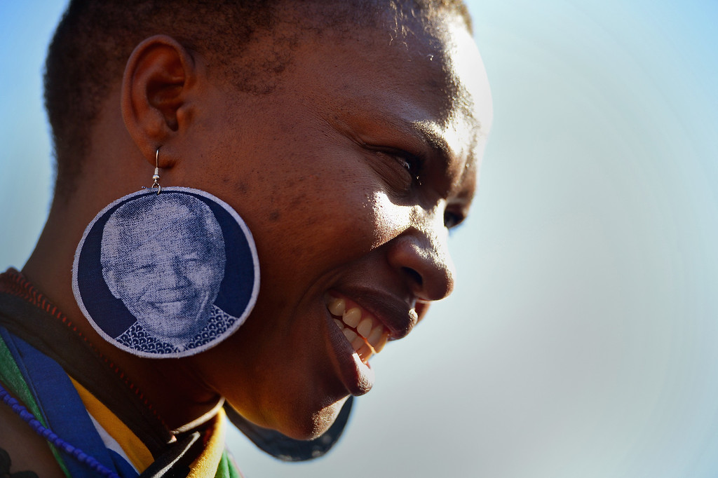 . PRETORIA, SOUTH AFRICA - JUNE 26:  A woman wearing earrings depicting former South African President Nelson Mandela joins other people gathering to leave messages of support for him outside the Mediclinic Heart Hospital June 26, 2013 in Pretoria, South Africa. South African President Jacob Zuma confirmed on June 23 that Mandela\'s condition has become critical since he was admitted to the hospital over two weeks ago for a recurring lung infection.  (Photo by Jeff J Mitchell/Getty Images)