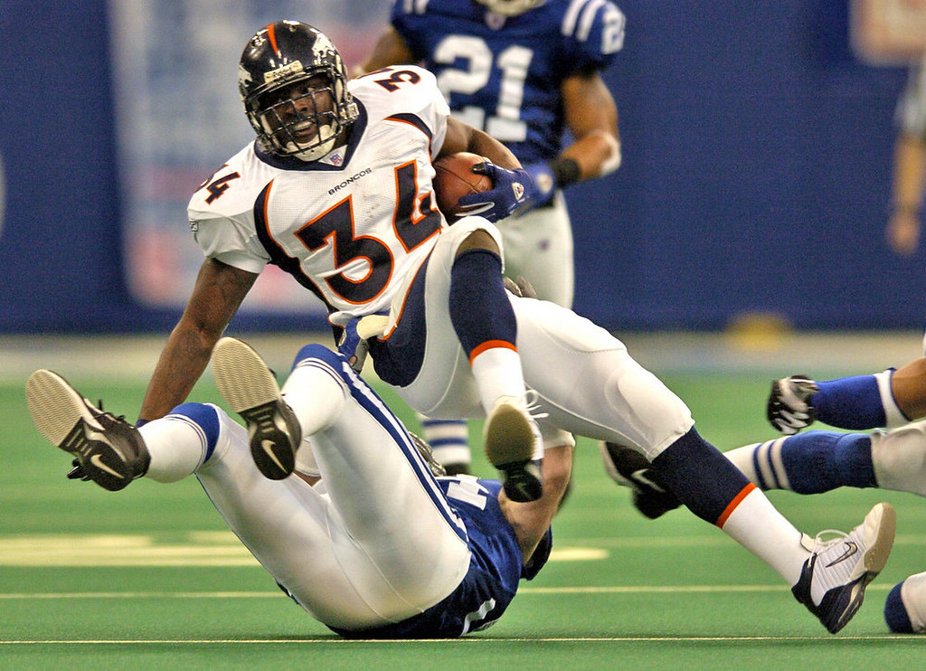 . Denver Broncos Reuben Droughns #34 gets spun around by Indianapolis Colts Rob Morris #94 after a two yard gain during the Sunday Wildcard Playoff game at the RCA Dome Sunday January 9, 2005. (DENVER POST PHOTO BY JOHN LEYBA)