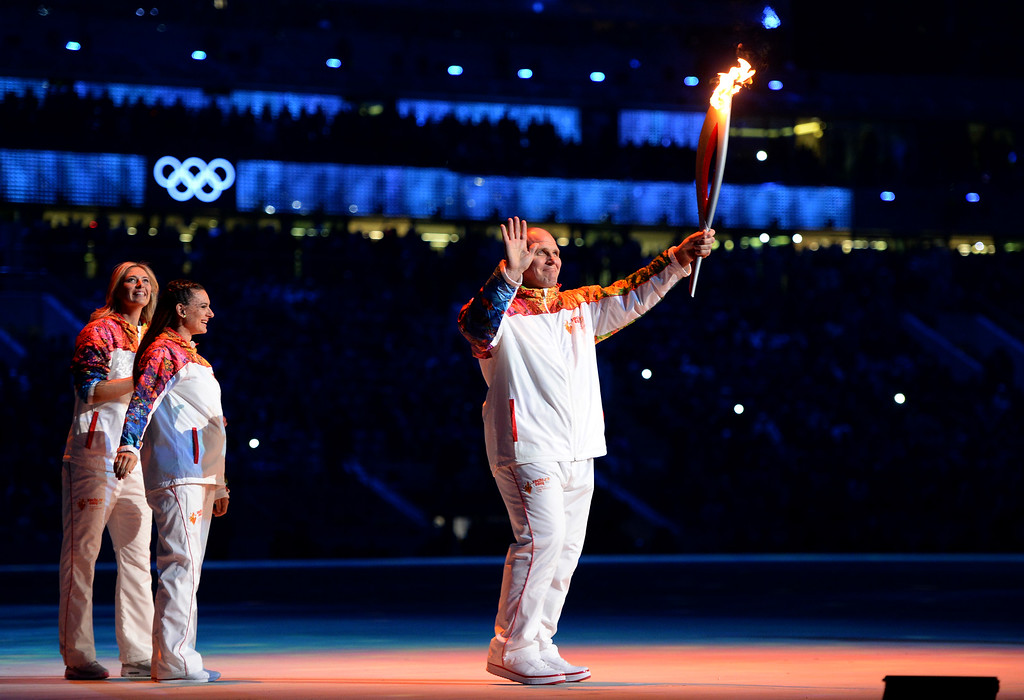 . Russian former wrestler Alexander Karelin holds up the Olympic torch next to Russian pole vaulter Yelena Isinbayeva (2nd L) and Russian tennis player Maria Sharapova (L) during the opening ceremony of the Sochi 2014 Winter Olympics at the Fisht Olympic Stadium on February 7, 2014, in Sochi, Russia. (Photo by Jung Yeon-Je - Pool/Getty Images)
