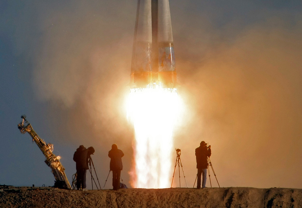 . Cameramen film as the Soyuz-FG rocket booster with Soyuz TMA-11M space ship carrying new crew to the International Space Station, ISS, blasts off at the Russian leased Baikonur cosmodrome, Kazakhstan, Thursday, Nov. 7, 2013. The rocket carrying the Olympic flame successfully blasted off from earth ahead of the Sochi 2014 Winter Games.  (AP Photo/Dmitry Lovetsky, File)