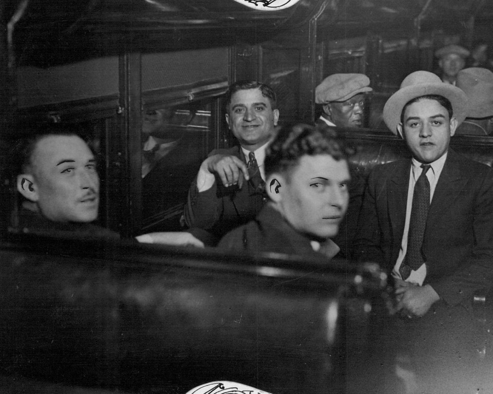 """. JUN 3 1932 - Prison-Bound Bootleggers constituted the majority of twenty-eight federal prisoners who were removed from the Denver county jail to the federal penitentiary at Leavenworth, Kan., Friday afternoon. Here are four \""""big shots\"""" of the rum business in Colorado, photographed in a prison car just before departure from the union station. Left to right, they are-Jack Ursetta, Roxie Stone, James Piccoli and James Marino. (Denver Post digital archive photo)"""