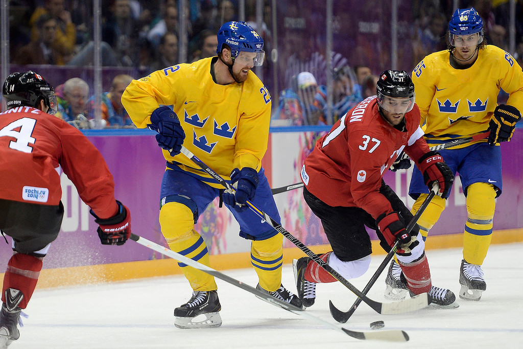 . Patrice Bergeron (37) of Canada and Daniel Sedin (22) of Sweden vie for the puck during the second period of the men\'s ice hockey gold medal game. Sochi 2014 Winter Olympics on Sunday, February 23, 2014 at Bolshoy Ice Arena. (Photo by AAron Ontiveroz/ The Denver Post)