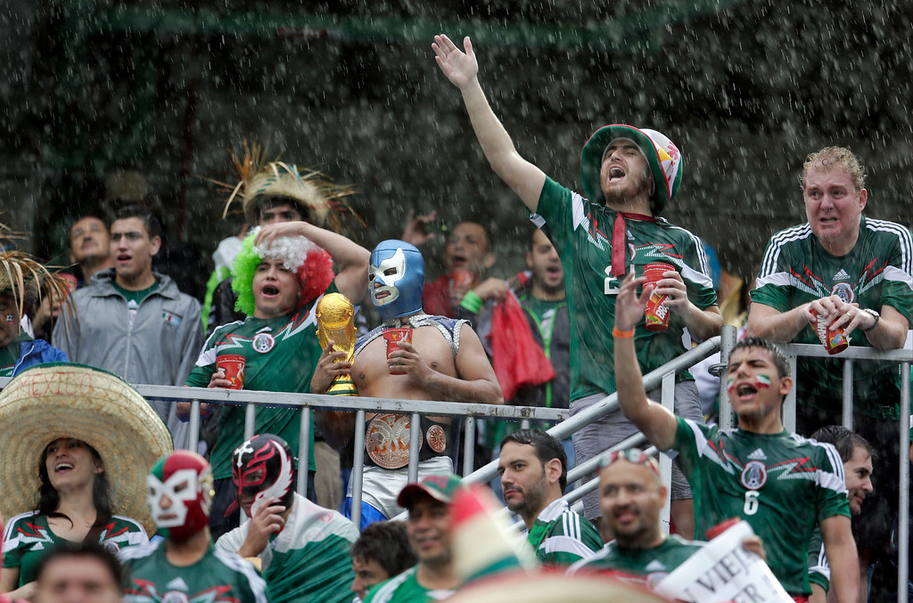 . Mexican fans cheer in a downpour before the group A World Cup soccer match between Mexico and Cameroon in the Arena das Dunas in Natal, Brazil, Friday, June 13, 2014.  (AP Photo/Petr David Josek)
