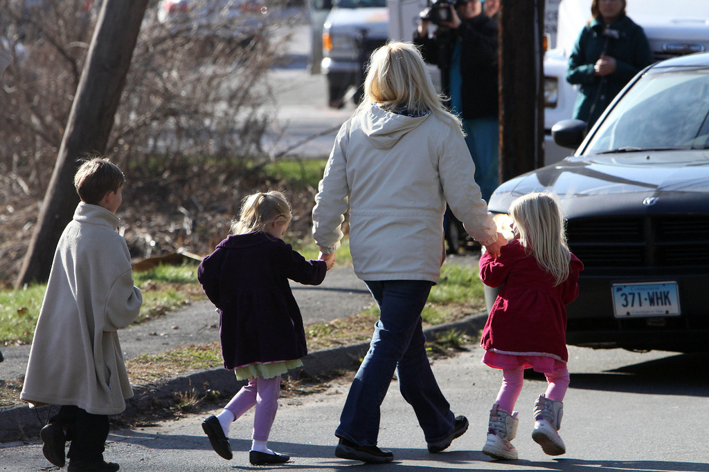 . Parents walk away from the Sandy Hook Elementary School with their children following a shooting at the school, Friday, Dec. 14, 2012 in Newtown, Conn. A man opened fire inside the Connecticut elementary school where his mother worked Friday, killing 26 people, including 18 children, and forcing students to cower in classrooms and then flee with the help of teachers and police. (AP Photo/The Journal News, Frank Becerra Jr.