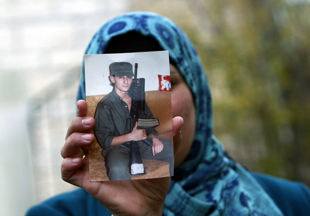 . Palestinian wife of Osama Al-Selawai holds an undated picture of him at their home in the West Bank city of Jenin, Monday, Dec. 30, 2013. Al-Selawai is one of 26 long-serving Palestinian prisoners who were convicted in connection to the killing of Israelis, that Israel announced it will release this week under a U.S.-brokered formula to resume Mideast peace talks. (AP Photo/Mohammed Ballas)
