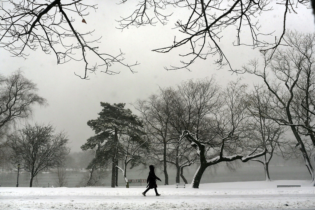 . A woman walks through a snow-shrouded park on March 8, 2013 in the Brooklyn borough of New York City. (Photo by Spencer Platt/Getty Images)