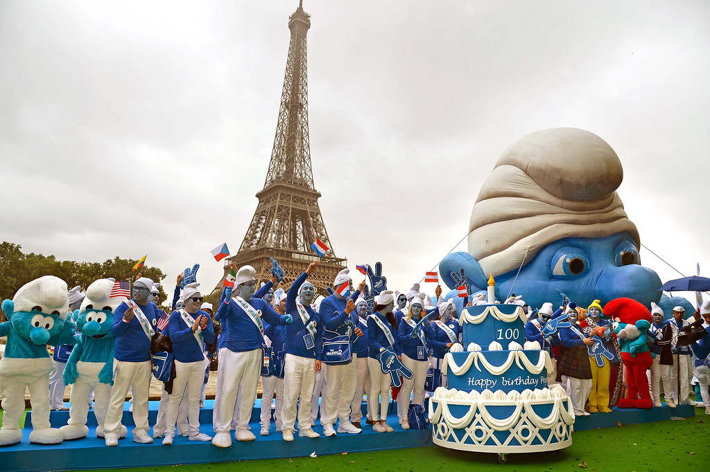 . Smurf Ambassadors pose by a giant Smurf character as part of Global Smurfs Day celebrations on June 22, 2013 on the Seine river bank in Paris, France. The Eiffel tower is seen behind.  (Photo by Pascal Le Segretain/Getty Images for Sony Pictures Entertainment)