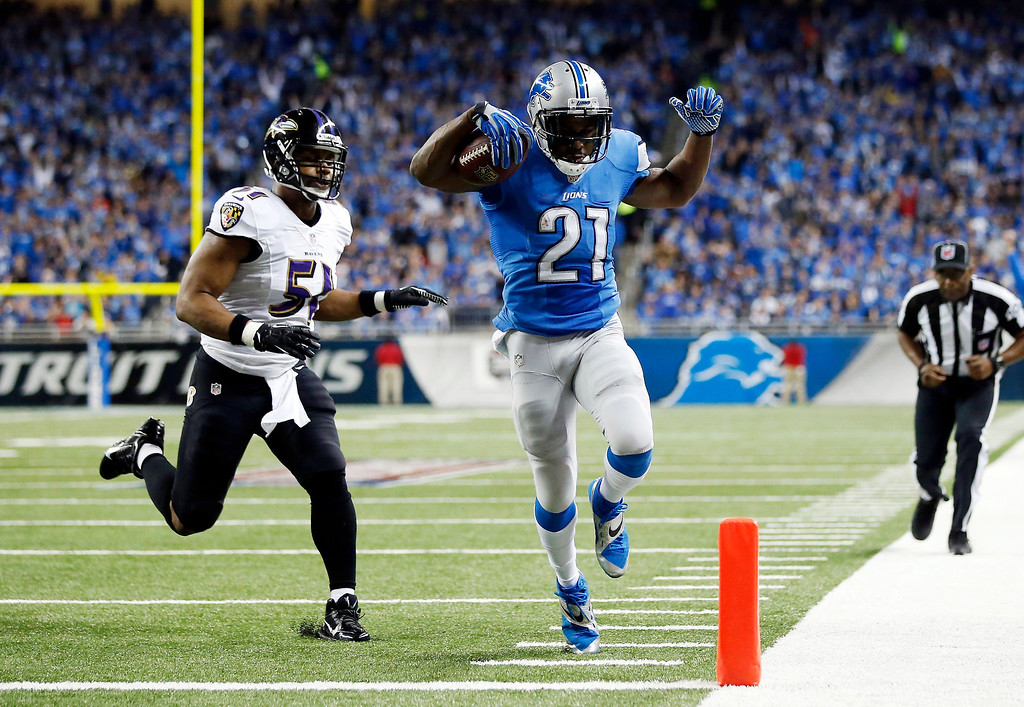 . Detroit Lions running back Reggie Bush (21) scores ahead of Baltimore Ravens inside linebacker Daryl Smith (51) for a 14-yard touchdown during the first quarter of an NFL football game in Detroit, Monday, Dec. 16, 2013. (AP Photo/Rick Osentoski)