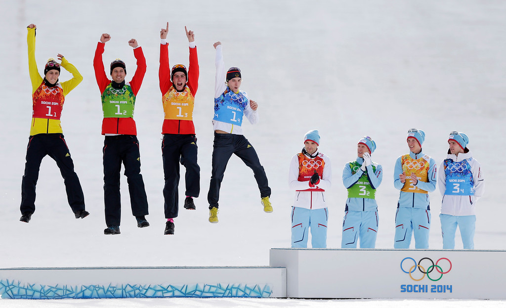. Germany\'s team Eric Frenzel, Bjoern Kircheisen, Johannes Rydzek and Fabian Riessle, from left, celebrate winning the silver as Norway\'s gold medal winners Magnus Hovdal Moan, Haavard Klemetsen, Magnus Krog and Joergen Graabak, from left, applaud during the flower ceremony of the  Nordic combined Gundersen large hill team competition at the 2014 Winter Olympics, Thursday, Feb. 20, 2014, in Krasnaya Polyana, Russia. (AP Photo/Matthias Schrader)
