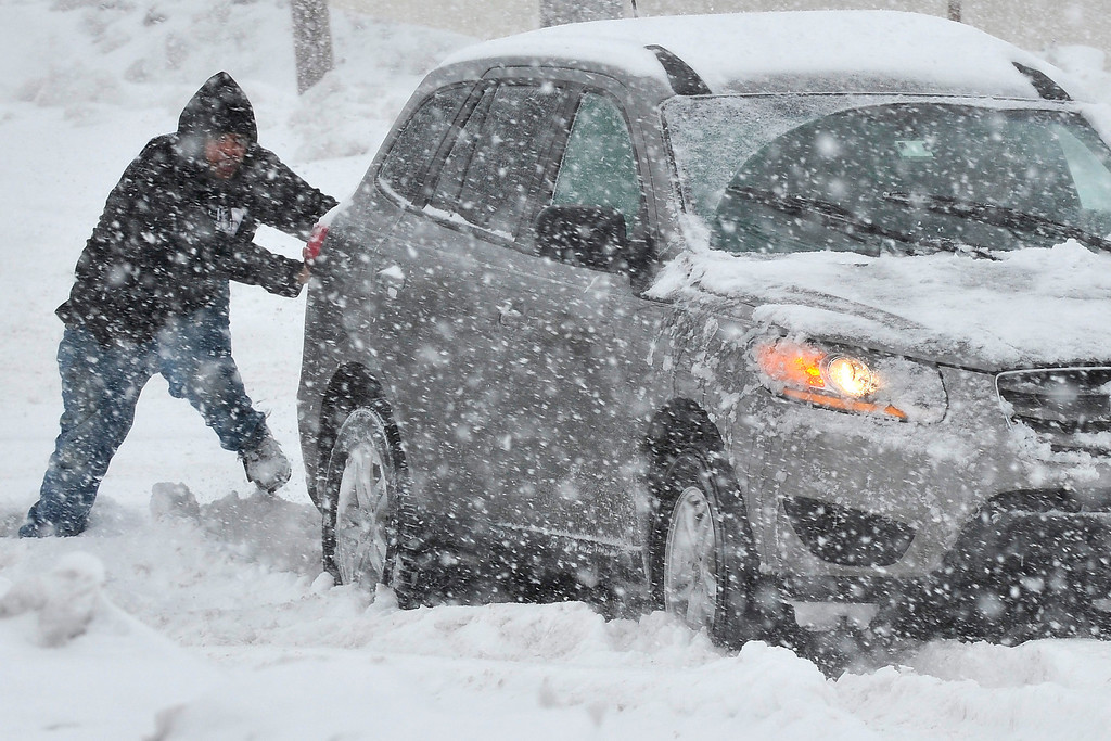 . A Good Samaritan in Bethlehem, Pa., helps push a stranded motorist stuck in deep snow on Stefko Boulevard Thursday, Feb. 13, 2014. A weather system arrived in Pennsylvania with the potential to be the biggest storm of an already memorable winter season.     (AP Photo/Chris Post)