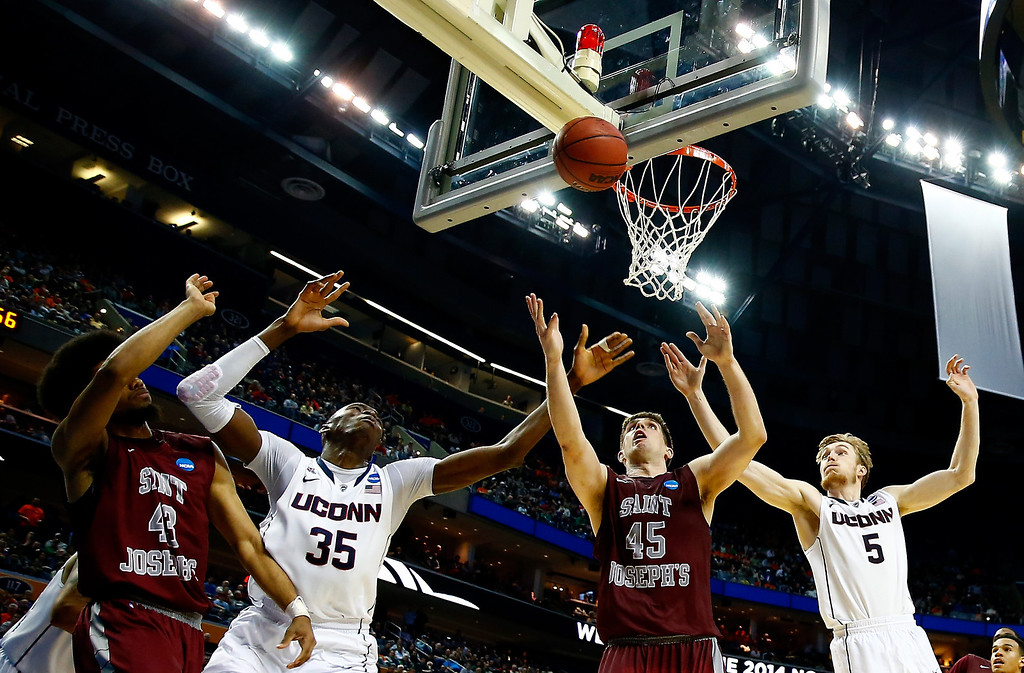 . BUFFALO, NY - MARCH 20:  Halil Kanacevic #45 of the Saint Joseph\'s Hawks and Amida Brimah #35 of the Connecticut Huskies go for a rebound during the second round of the 2014 NCAA Men\'s Basketball Tournament at the First Niagara Center on March 20, 2014 in Buffalo, New York.  (Photo by Jared Wickerham/Getty Images)