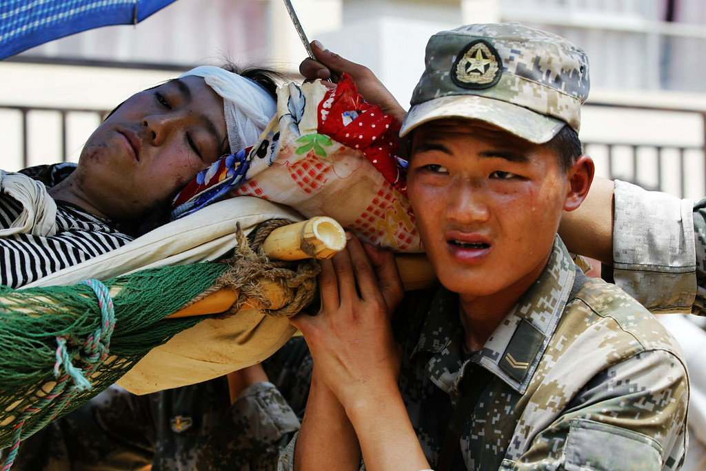 . In this photo provided by China\'s Xinhua News Agency, rescuers transfer an injured woman in the quake-hit Longquan village of Ludian county, southwest China\'s Yunnan Province, Tuesday, Aug. 5, 2014.   (AP Photo/Xinhua, Xing Guangli)