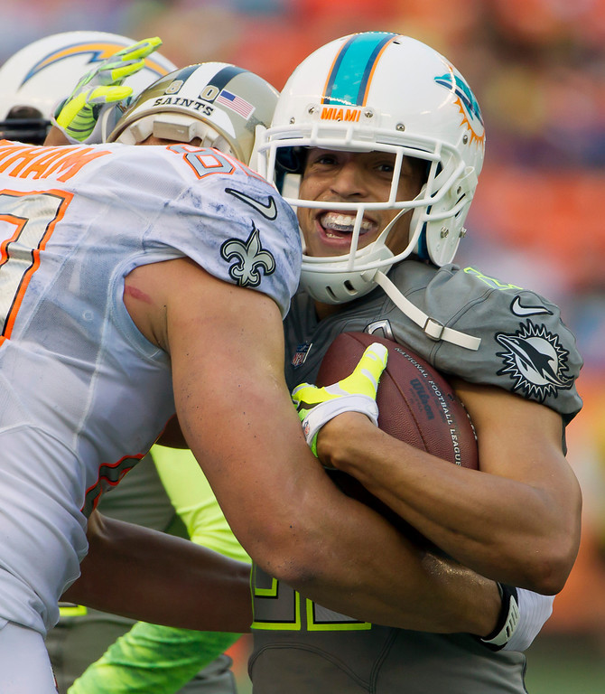 . New Orleans Saints tight end Jimmy Graham, left, of Team Rice congratulates Miami Dolphins corner back Brent Grimes, right, of Team Sanders, on his pass interception late in the fourth quarter of the NFL Pro Bowl football game Sunday, Jan. 26, 2014, in Honolulu. (AP Photo/Eugene Tanner)