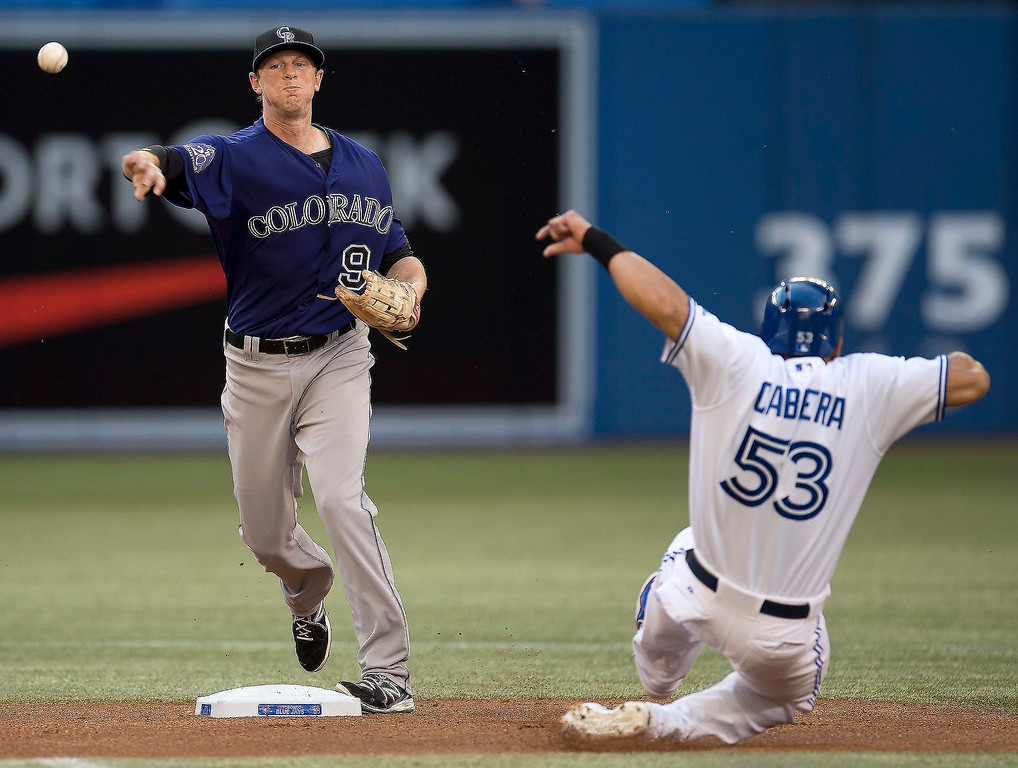. Colorado Rockies\' DJ LeMahieu, left,  throws to first to complete a double play, after forcing out Jose Bautista, right,  at second during first inning of a baseball game in Toronto, Monday June 17, 2013.  (AP Photo/The Canadian Press, Frank Gunn)