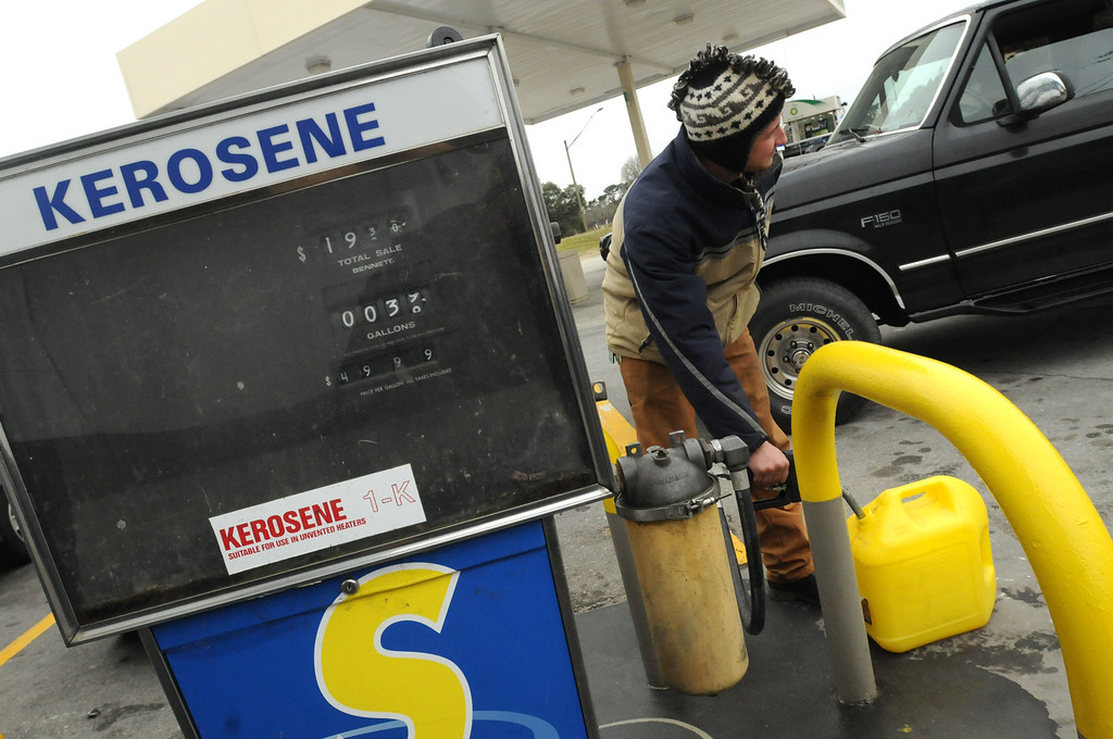 . A.J. Libero pumps kerosene in Leland, N.C., Tuesday Jan 28, 2014. Residents are preparing for the winter storm that is approaching the area overnight by fueling up and buying supplies at local stores.   Snow, sleet and freezing rain are expected across much of North Carolina.  (AP Photo/The Star-News, Ken Blevins)