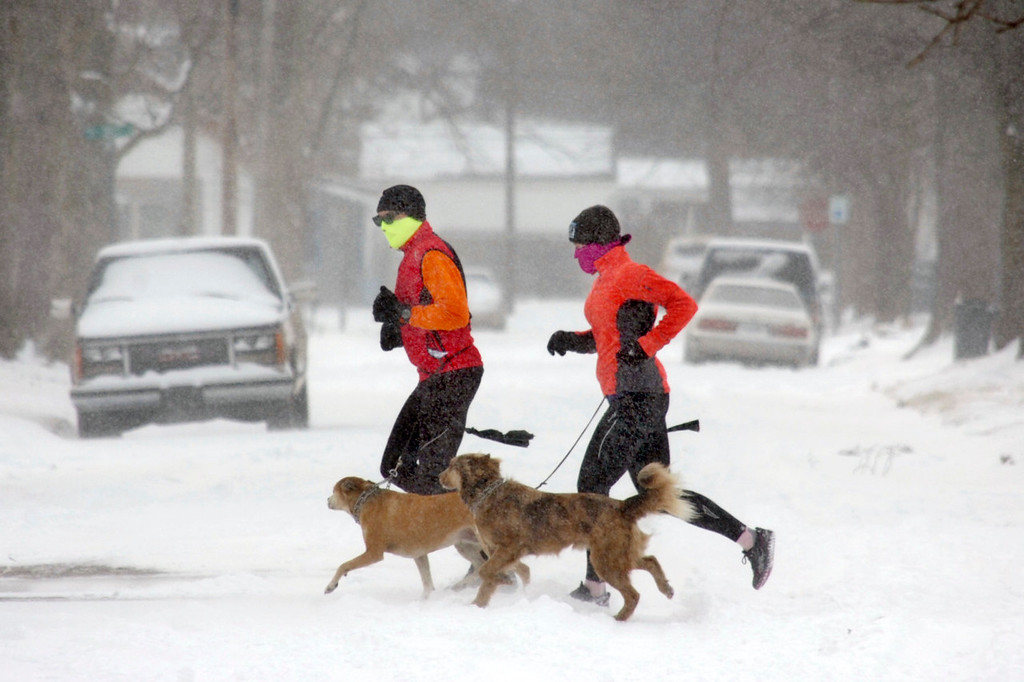 . Tim Esh, left, and Katie Karnehm run in the snow with Karnehm\'s dogs, Bailey, left, and Archimedes in Marion, Ind., on Thursday, Jan. 2, 2014. Most of Indiana was under a winter weather advisory Thursday from the National Weather Service.  (AP Photo/The Chronicle-Tribune, Jeff Morehead)