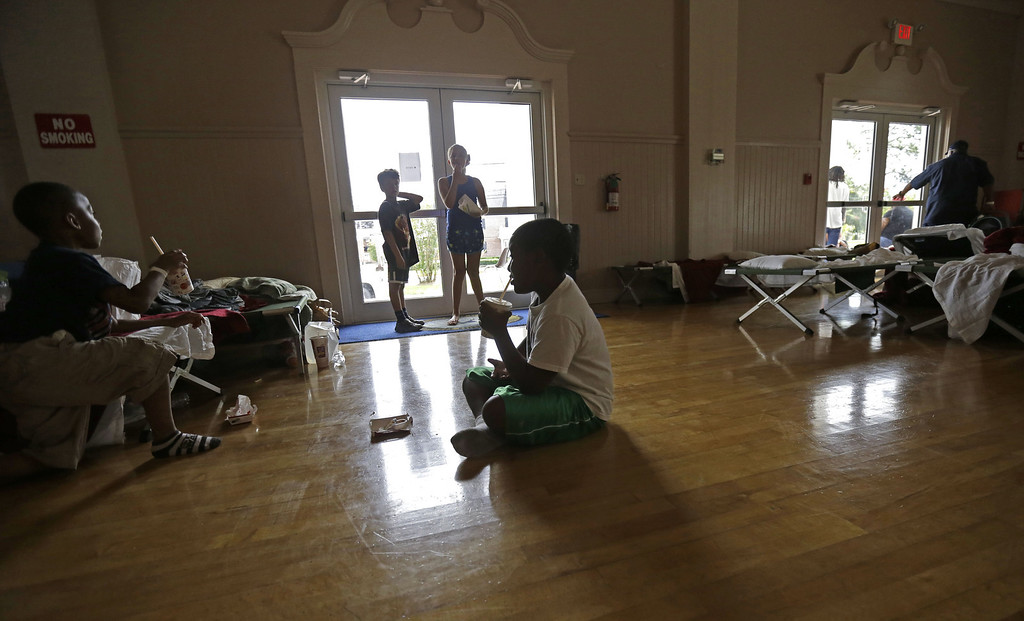 . Tylon Harvey, 10, form Phoenix, La., sips a drink inside an evacuation shelter in Belle Chasse, La., in anticipation of Tropical Storm Karen, Saturday, Oct. 5, 2013. The East Bank of Plaquemines Parish has been under a mandatory evacuation, which has been downgraded to a voluntary evacuation. (AP Photo/Gerald Herbert)