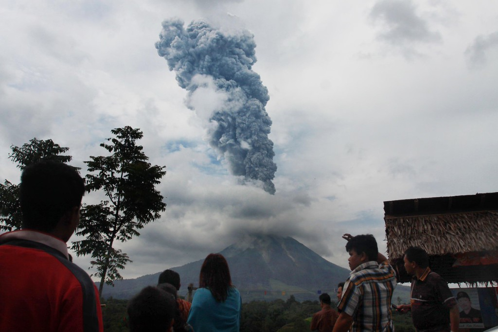 . Residents watch as a giant plume of steam and ash rise and hot lava rolls from the crater of Mount Sinabung volcano during an eruption as seen from Karo district in Indonesia\'s Sumatra island on November 5, 2013.   AFP PHOTO / STRSTR/AFP/Getty Images