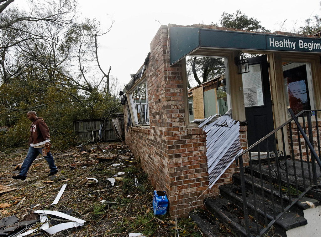 . Brandon Richardson removes debris from the Healthy Beginning by Sonyia hair salon following a winter storm in Mobile, Alabama, December 20, 2012. The first major winter storm of the year took aim at the U.S. Midwest on Thursday, triggering high wind and blizzard warnings across a widespread area, and a threat of tornadoes in Gulf Coast states to the south. REUTERS/Jon Hauge