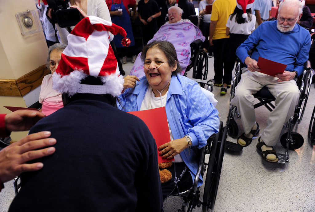 . Linda Gonzales, is greeted by Maria Carrillo, 9, after students and parents from the Denver Center for International Studies at Ford Elementary School spend a Saturday singing holiday songs in three different languages to the residents of the Kindred Care nursing home. (Photo by Kathryn Scott Osler/The Denver Post)