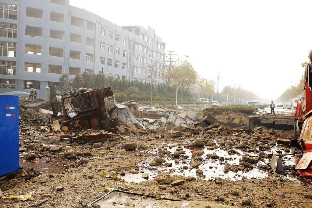 . Chinese rescuers search for victims after an oil pipeline exploded, ripping roads apart, turning cars over and sending thick black smoke billowing over the city of Qingdao, east China\'s Shandong province on November 22, 2013, killing 35 people, authorities said, in the latest deadly industrial accident in the country.    AFP PHOTOSTR/AFP/Getty Images