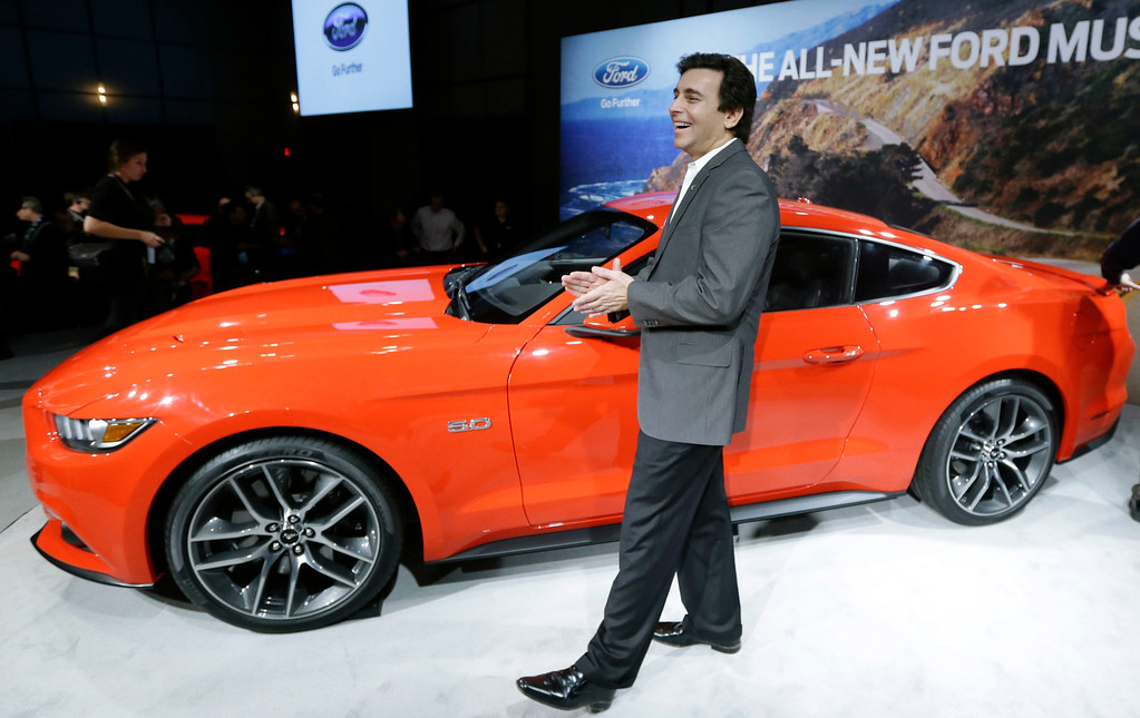 . Mark Fields, left, chief operating officer for Ford Motor Company, stands next to the automaker\'s new 2015 Ford Mustang in Dearborn, Mich., Thursday, Dec. 5, 2013. The Mustang is celebrating its 50th birthday with a new design the automaker plans on taking global. It goes on sale next fall in North America and will arrive later in Europe and Asia. (AP Photo/Carlos Osorio)
