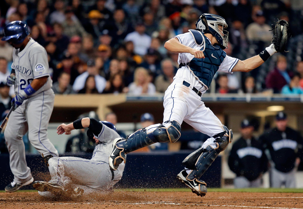 . San Diego Padres catcher Nick Hundley reaches for a late and wide throw as Colorado Rockies\' Michael Cuddyer slides in with the tying run  i  the eighth inning of  a baseball game Friday April 12, 2013 in San Diego. (AP photo/Lenny Ignelzi)