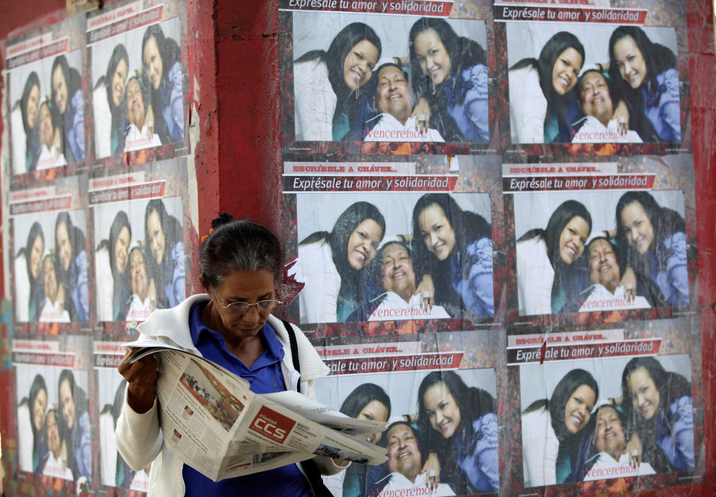 """. A woman reads a newspaper as she stands by a wall covered with posters showing Venezuela\'s President Hugo Chavez pictured with his daughters Maria Gabriela, and Rosa Virginia, outside the military hospital in Caracas, Venezuela, Tuesday, March 5, 2013. A brief statement read on national television by Communications Minister Ernesto Villegas late Monday carried the sobering news about the charismatic 58-year-old leader\'s deteriorating health. Villegas said Chavez is suffering from \""""a new, severe infection.\"""" The state news agency identified it as respiratory. (AP Photo/Ariana Cubillos)"""