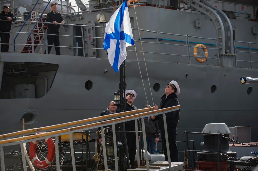 . Officers of the Ukrainian navy ship Lutsk raise a Russian navy flag aboard the Lutsk, which has been seized by Russia, in Sevastopol, Thursday, March 20, 2014.  (AP Photo/Andrew Lubimov)