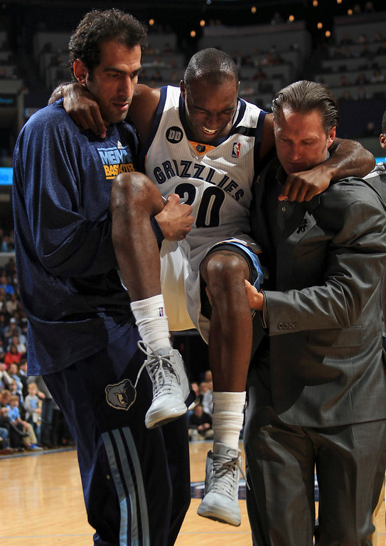. Memphis Grizzlies guard Quincy Pondexter (20) is helped off the court by Grizzlies center Hamed Haddadi (L) of Iran and head athletic trainer Drew Graham (R) during the second half of their NBA basketball games against the Denver Nuggets in Memphis, Tennessee December 29, 2012. The Grizzlies defeated the Nuggets 81-72.  Pondexter left the game with a left MCL strain and did not return.  Pondexter is scheduled for an MRI in the morning.  REUTERS/Nikki Boertman