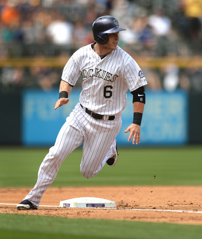 . DENVER, CO - JULY 5: Colorado baserunner Corey Dickerson rounded third on the way to scoring in the first inning. Dickerson bounced a ball over the center field fiend for a ground rule double to get on base. The Colorado Rockies hosted the Los Angeles Dodgers at Coors Field Saturday afternoon, July 5, 2014.  Photo by Karl Gehring/The Denver Post