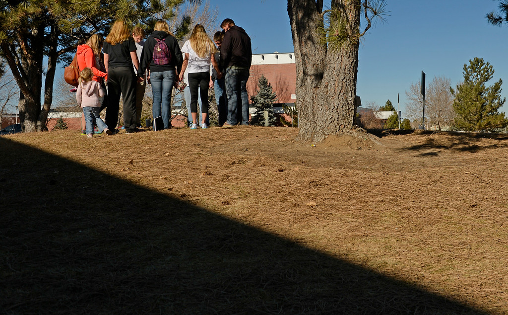 . Members of Grace Chapel in Englewood pray outside Arapahoe High School in Centennial, December 16, 2013. The school was the scene of a shooting on Friday that left a student gunman dead and two other students injured. (Photo by RJ Sangosti/The Denver Post)