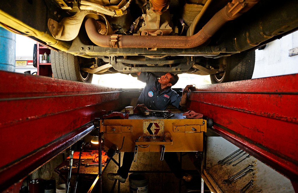 . Julio Vergara works on doing and oil change, at a Grease Monkey in east Denver, on a truck owned by active army soldier Luke Goeckner, November 11, 2013. Veterans got a free oil change at many Grease Monkey locations for Veterans Day. (Photo By RJ Sangosti/The Denver Post)