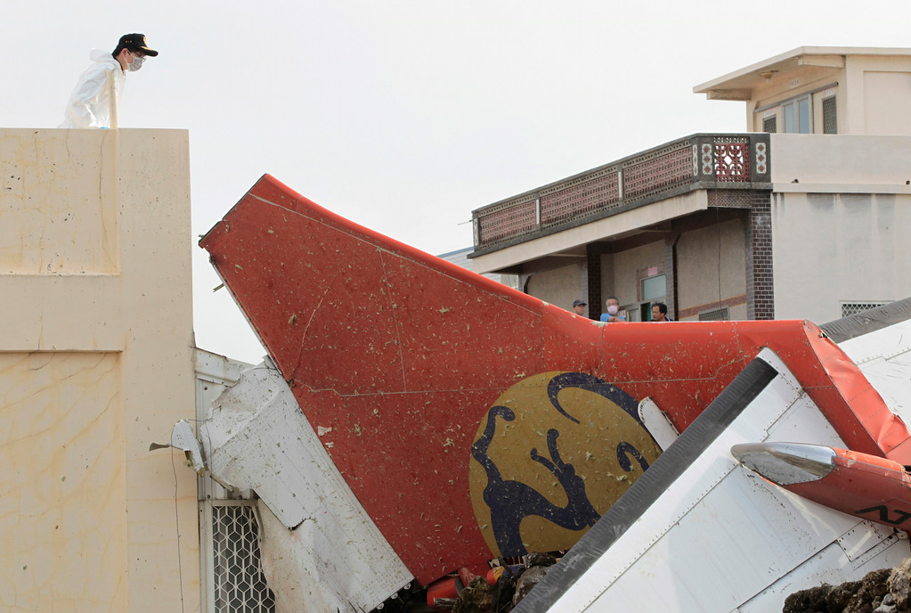 . A special investigator inspects the tail wing of crashed TransAsia Airways flight GE222 on the outlying island of Penghu, Taiwan, Thursday, July 24, 2014. (AP Photo/Wally Santana)