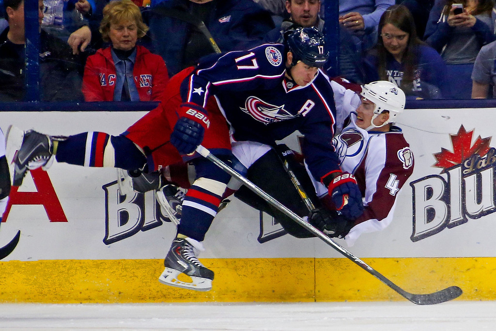 . COLUMBUS, OH - APRIL 1:  Brandon Dubinsky #17 of the Columbus Blue Jackets checks Tyson Barrie #4 of the Colorado Avalanche while chasing after the puck during the first period on April 1, 2014 at Nationwide Arena in Columbus, Ohio. (Photo by Kirk Irwin/Getty Images)