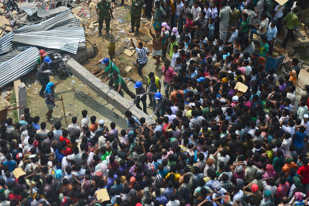 . Bangladeshi volunteers and rescue workers assist in rescue operations after an eight-story building collapsed in Savar, on the outskirts of Dhaka, on April 25, 2013.  AFP PHOTO/Munir uz ZAMAN/AFP/Getty Images