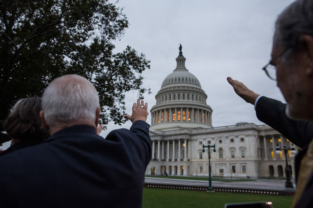 . WASHINGTON, DC - OCTOBER 16:  Religious leaders raise their hands in prayer towards the Capitol Building on the morning of October 16, 2013 in Washington, DC. Today marks the 16th day of the government shutdown and the last day to find a solution before the government could potentially begin defaulting on debts.  (Photo by Andrew Burton/Getty Images)