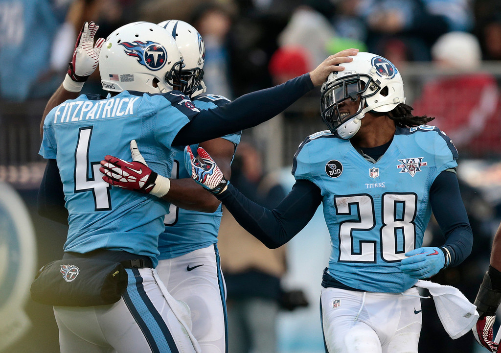 Description of . Tennessee Titans running back Chris Johnson (28) is congratulated by quarterback Ryan Fitzpatrick (4) after scoring a touchdown against the Arizona Cardinals on a 25-yard pass play in the first quarter of an NFL football game Sunday, Dec. 15, 2013, in Nashville, Tenn. (AP Photo/Wade Payne)