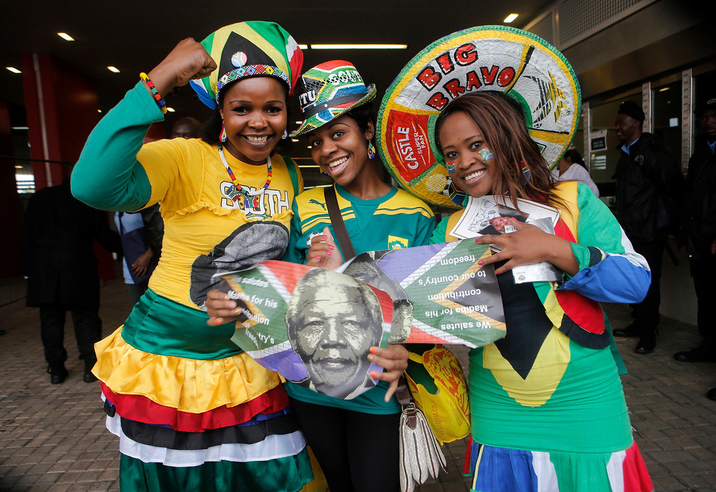 . Women pose for a photo as they arrive for  the memorial service the memorial service for former South African president Nelson Mandela at the FNB Stadium in Soweto, near Johannesburg, South Africa, Tuesday Dec. 10, 2013. (AP Photo/Tsvangirayi Mukwazhi)